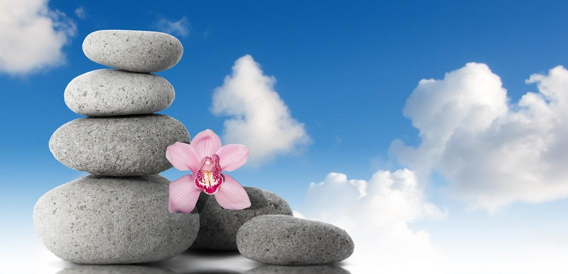 Zen stones with orchid flower with blue sky and clouds background