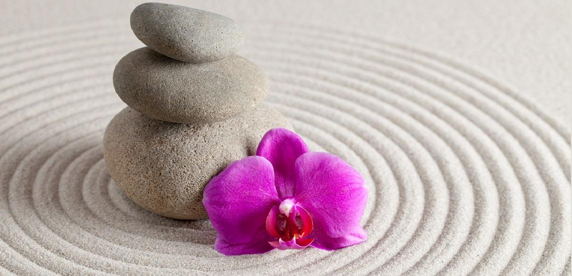 Zen stones with orchid flower on rippling sand